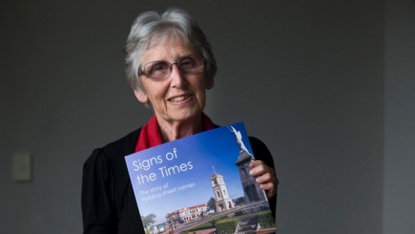 Dorothy Pilkington holding up her book 'Signs of the Times'
