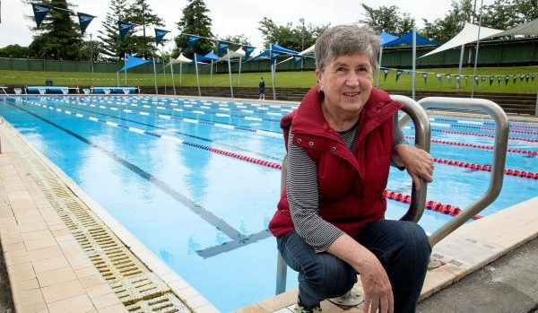 Val Mills in front of an outdoor swimming pool